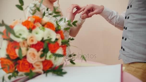 Bellezza sposa e sposo bello indossano anelli dorati vicenda davanti al bouquet da sposa. Cerimonia di matrimonio.