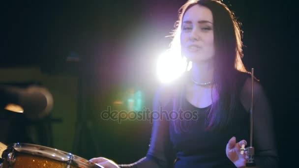 Bubeník temperamentní dívka s černými vlasy v garáži - rocková kapela