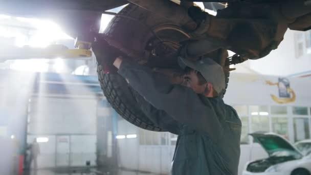 Garázs autó szolgáltatás - alatt a alja autó szerelő ellenőrzi a kerék, közelről