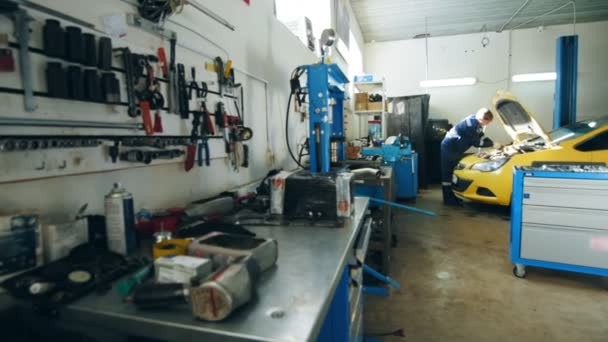 Small car garage - auto mechanic checks engine in hood of yellow car