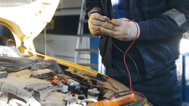 Mechanik v rukavicích kontroluje electro pojistka relé - elektrické komponenty v autě - automobilový servis Diagnostika