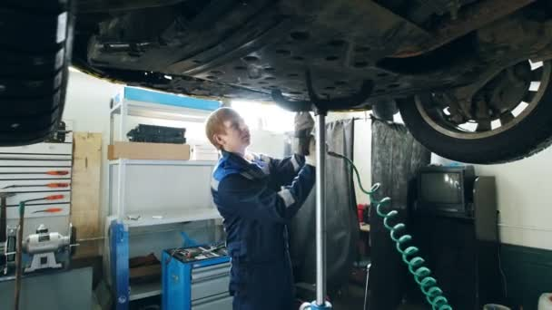 Garázs autószervíz - szerelő kibontani az alján a felemelt autó, a kis üzleti