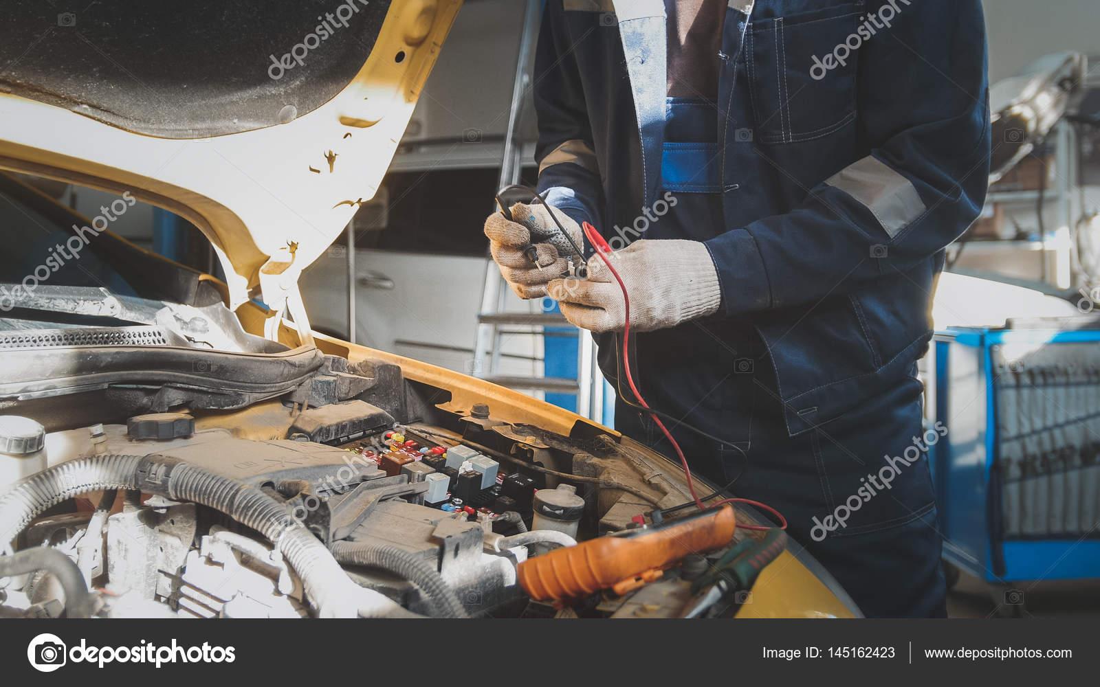 Mechaniker arbeitet mit Voltmeter - Auto-Elektrik - elektrische ...