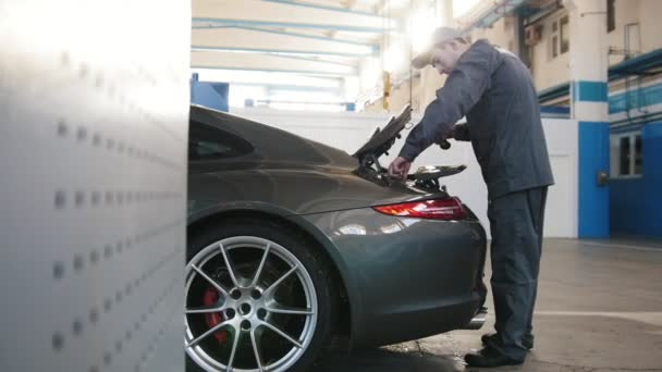 Mechanic In Car Workshop Checking And Repairing Compartment For
