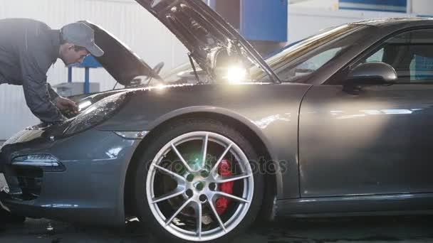 Mechanik v auto servis - opravy v motorovém prostoru pro luxusní sportovní automobil - jezdec výstřel