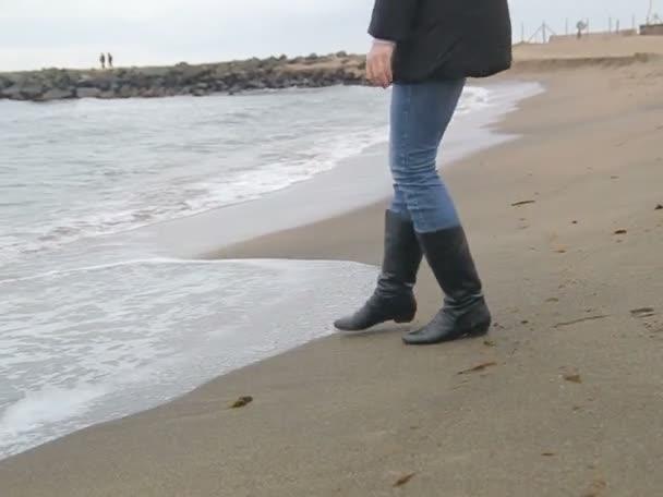 Žena na studené ledové pláži hrát s vlnami moře