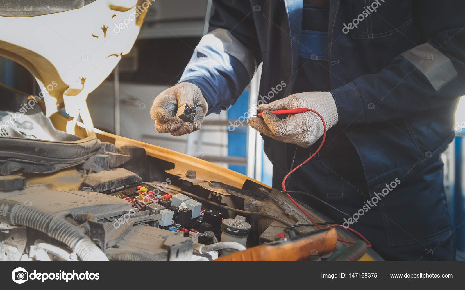 Mechanic in auto workshop works with car electrics - electrical ...