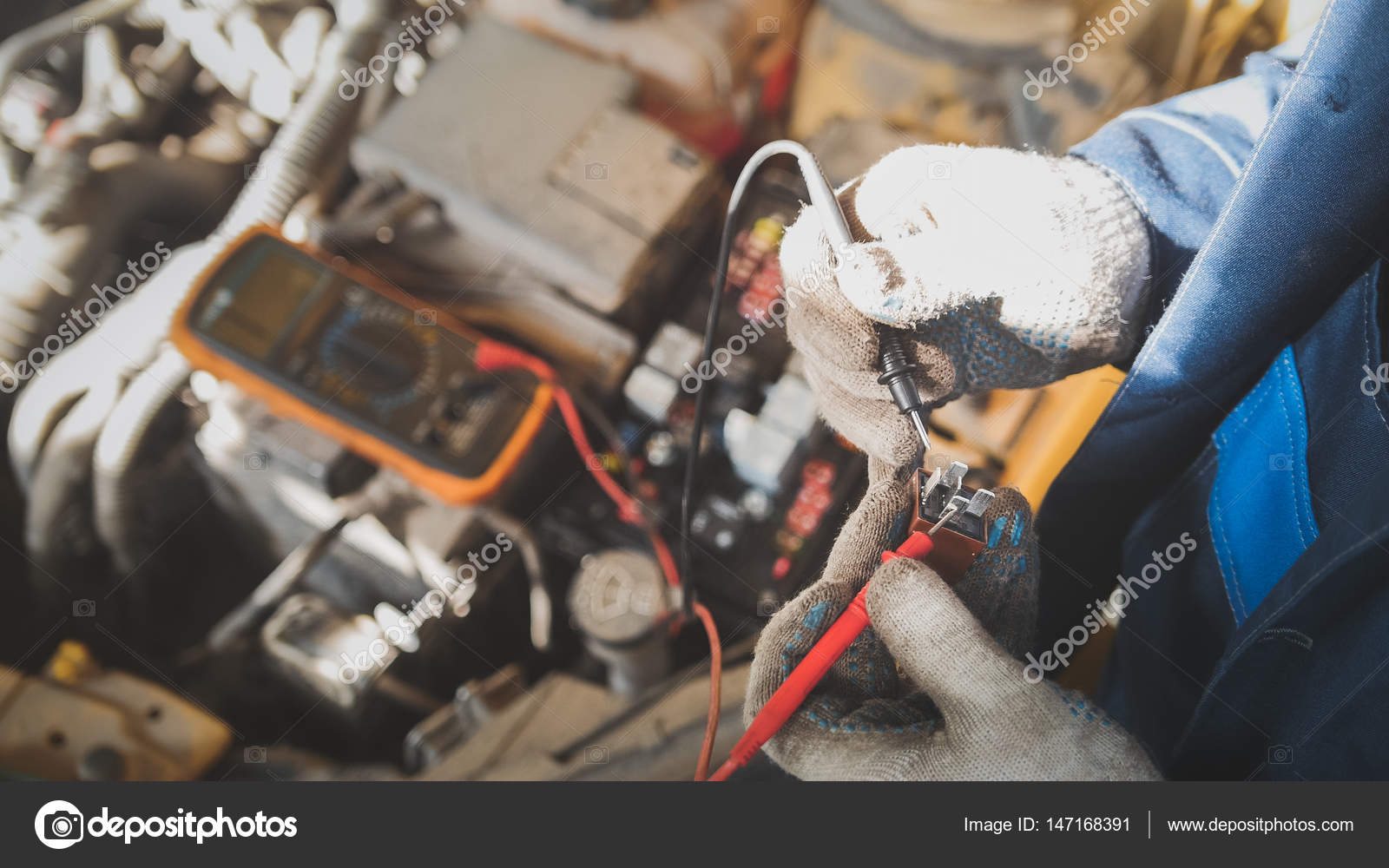 Mechanic in auto workshop works with car electrics ... on