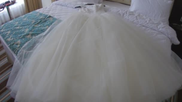 Svatební bílé šaty na posteli