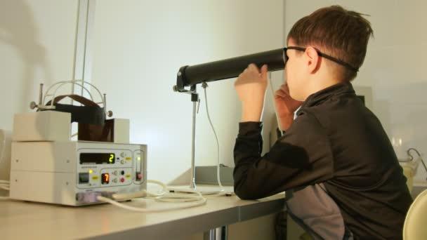 Boy checks eye vision in ophthalmology clinic