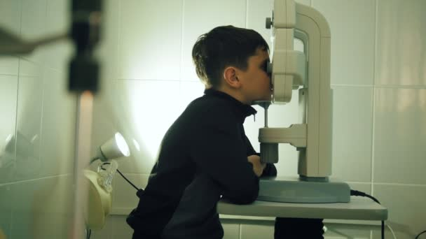 Boy checks eye vision in ophthalmology clinic - close up