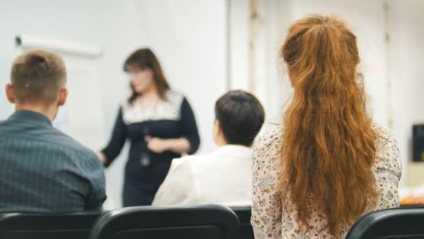 Mluvčí ženské říká a ukazuje prezentace pro posluchače v obchodní hale