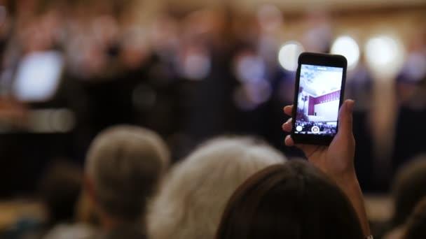 Zuschauerraum bei Konzert - Menschen filmen Auftritt mit Smartphone, Musikoper