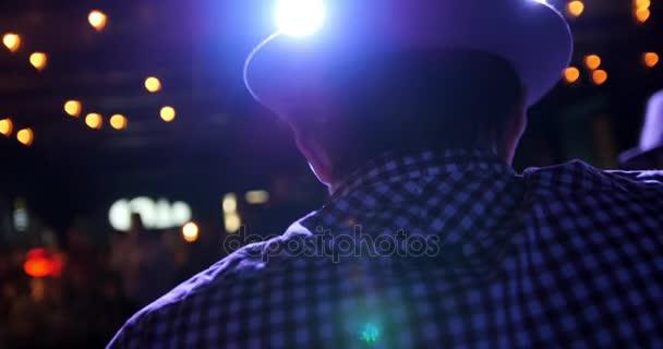 Kytarista na scéně v baru - hudebník v hat hraje kytara, zadní pohled