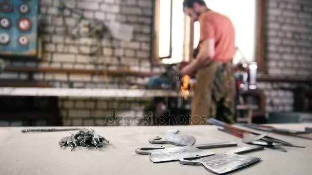 Man maalt metalen ijzeren gereedschap met sparkles smeden