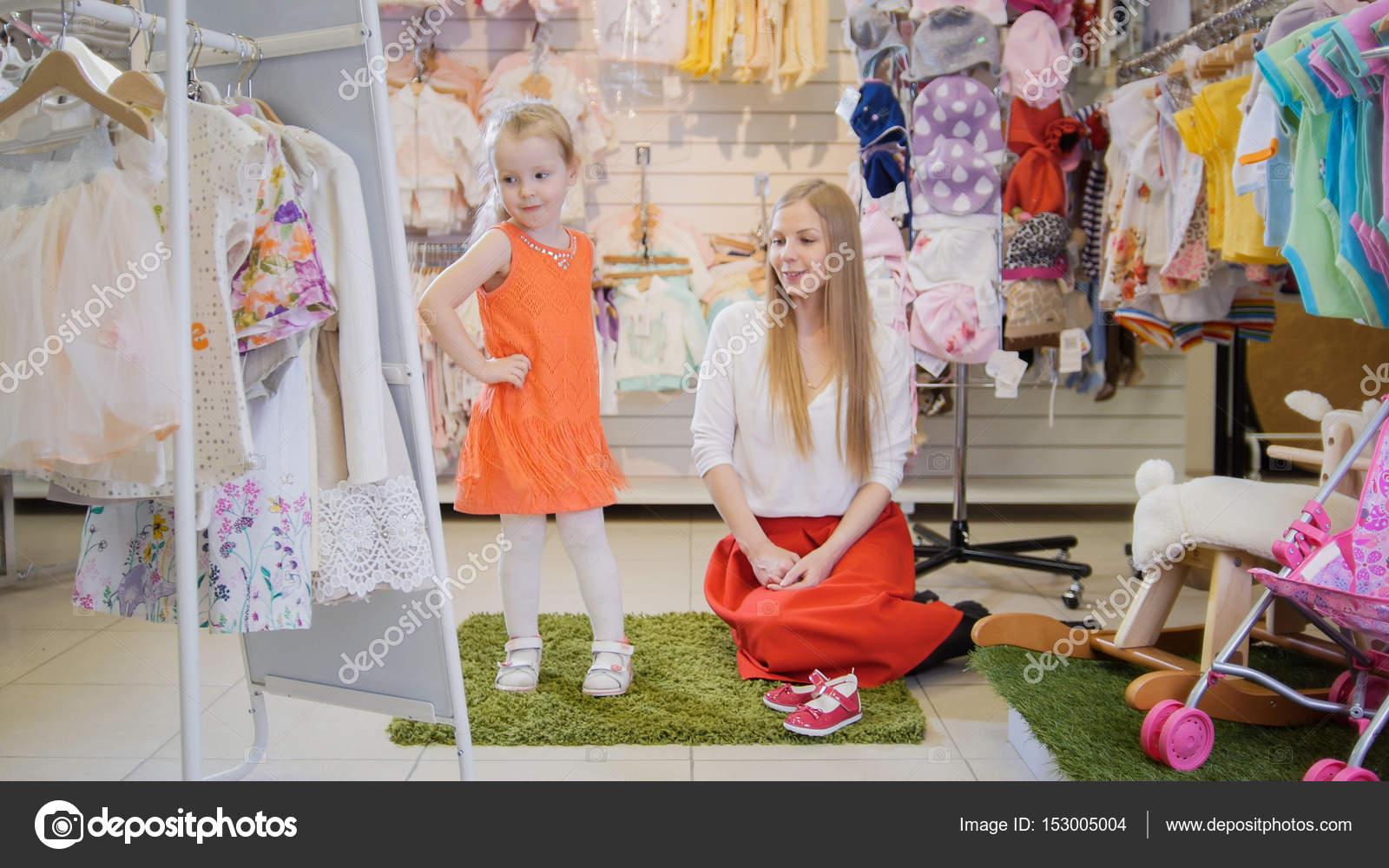 c323d8e9034 Las niñas de compras - rubia niña con mamá elige Vestido de la manera en la  tienda de ropa de niños