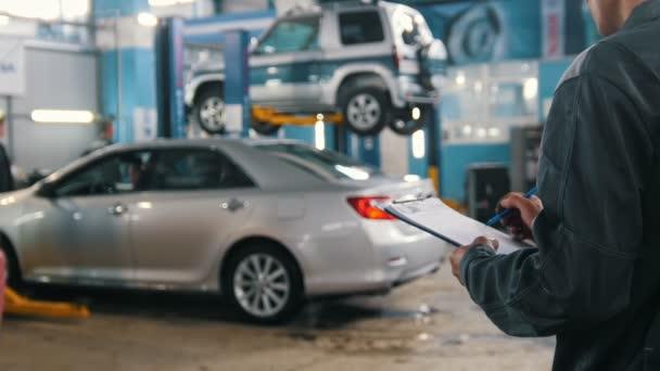 Szerelő ellenőrzi része az autó a garázsban műhely - autószervíz