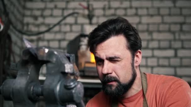 Blacksmith bends metal knife with gripe in workshop forge, portrait
