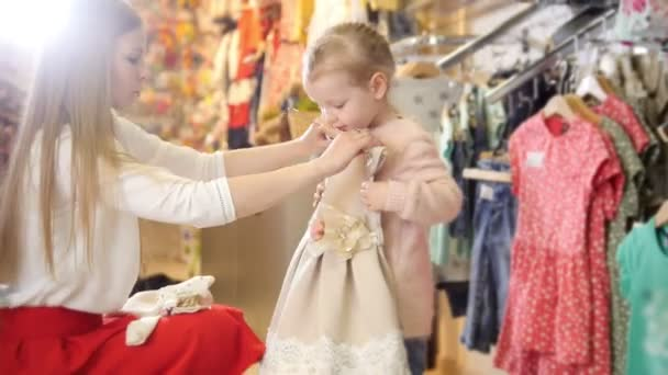 edfb0f3766da1 Shopping for kids - cute little girl with mommy buying dress in store of kids  clothes– stock footage