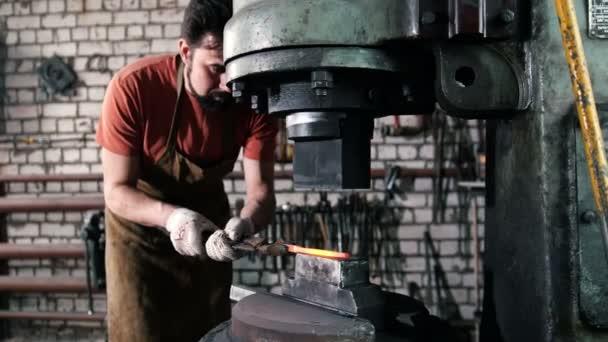 der Schmied, der mit dem Gegenstand arbeitet, wird vom Feuer entfernt