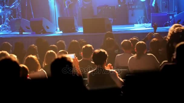 Dav diváků v hledišti na rockovém koncertě, de-zaměřené
