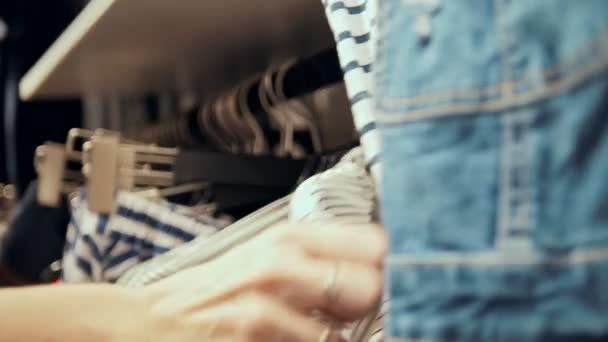 Butik - Zenske ruky poblíž závěsy s Dámské oblečení v obchoďáku