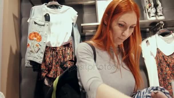 cac612355145b Девушка выбирает одежду среди различных Женская одежда– стоковое видео