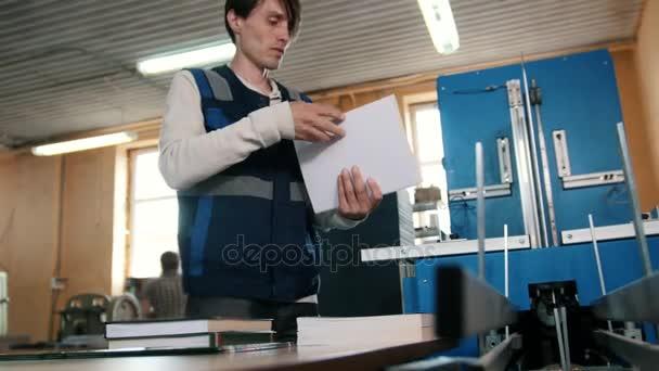 Dělník v tiskárně se zabývá tiskem