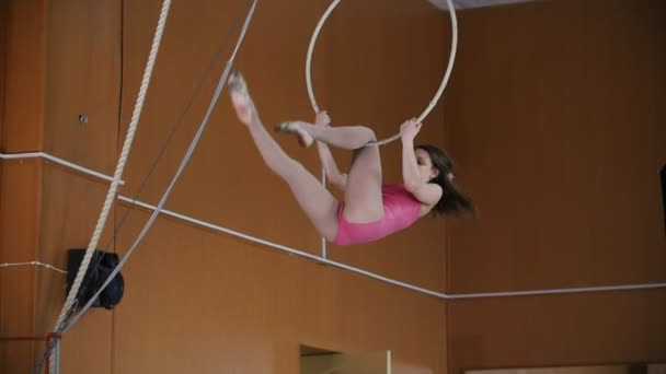 Young woman acrobat in pink suit perform exercise on gymnastics hoop - slow-motion