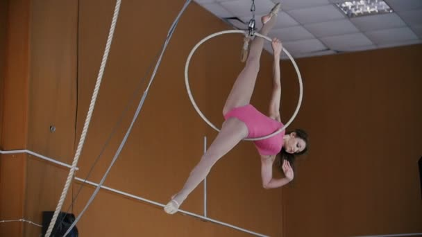 Young girl acrobat shows flexibility on gymnastic hoop - slow-motion
