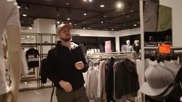 Nakupování, móda, styl - vousy mladý muž je volba cap v obchoďáku nebo obchod s oblečením