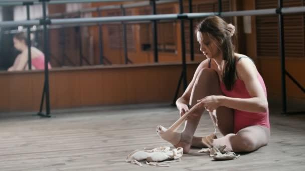 Balletttänzerin zieht ihre Ballettschuhe an