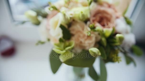 Golden rings on colourful wedding bouquet - standing at window