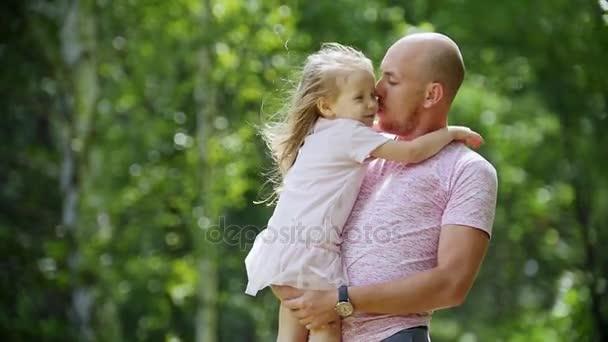 Boldog apja átölelve és a lengő a lánya park, lassú mozgás