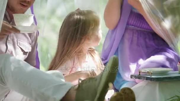 Šťastná rodina posnídat venku v zeleném parku - matka, otec a dcera