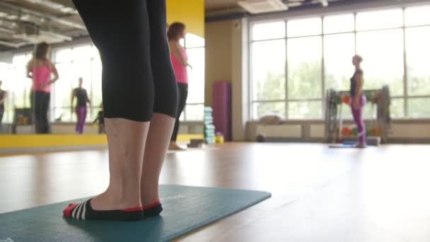 Školení jógy pro skupinu zralých žen v tělocvičně, jezdec výstřel
