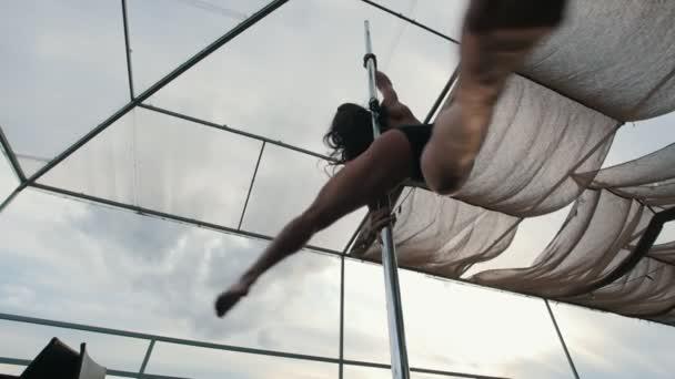 Atraktivní holka tanečník s tekoucí vlasy otočená kolem pólu - pomalý pohyb, pohled zespodu