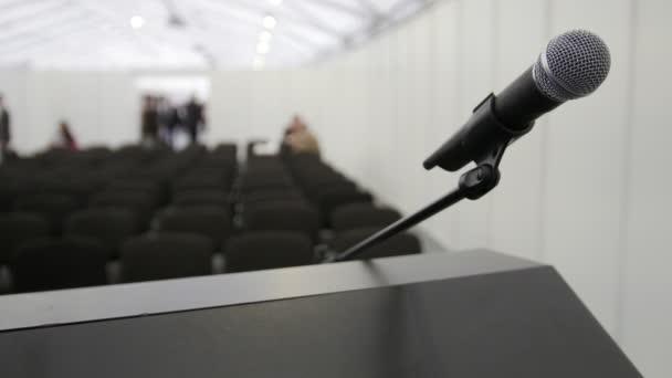 Konference, přednášky - mikrofon na jevišti v sále čeká na vystoupení, zblízka