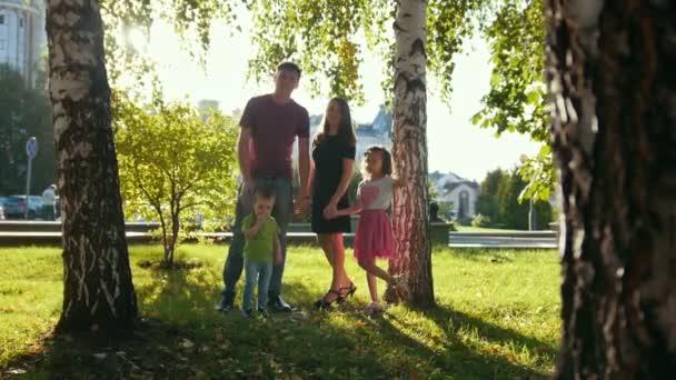 Zdravá rodina v parku na letní večer - otec, Máma, Dcera a chlapeček