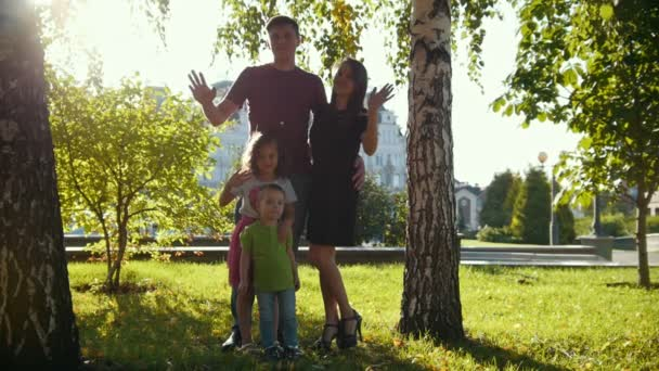 Healthy family in a park at summer evening - father, mammy, daughter and little boy, clow-motion