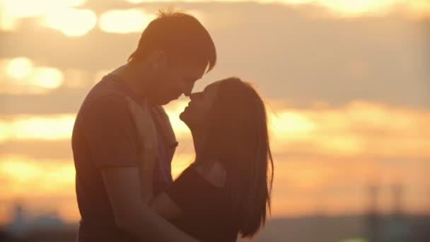 Portrét milující pár - muž a žena při západu slunce - polibek