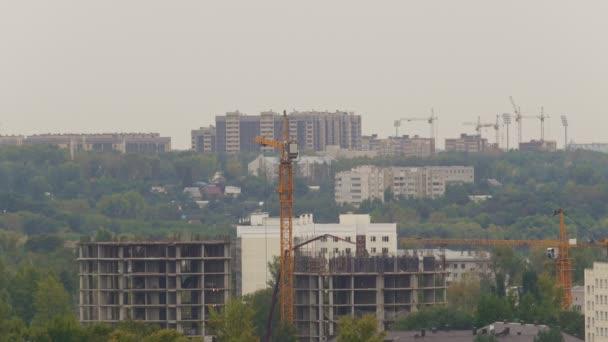 Staveniště s pracovníky, jeřáb a nedokončené stavby