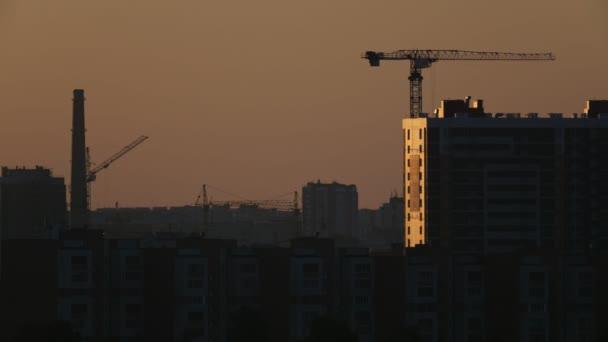 Stavební jeřáby poblíž bytovými jednotkami - zobrazit na východ slunce