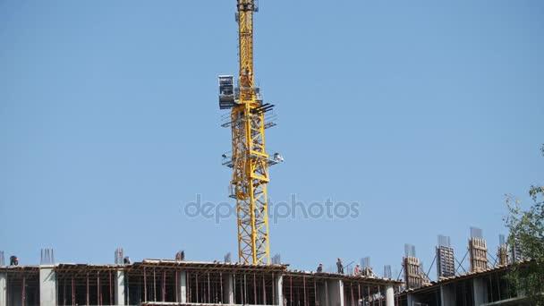 Jeřábové práce na staveništi - moderní bydlení stavební - zaměstnanci