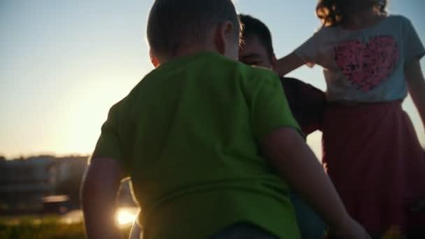 Zdravá rodina chůzi venkovní - málo bělochů boy batole hraje a směje se s otcem a sestrou, pomalý pohyb