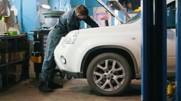 Mechanik v servisu auto - oprava pro bílé Suv