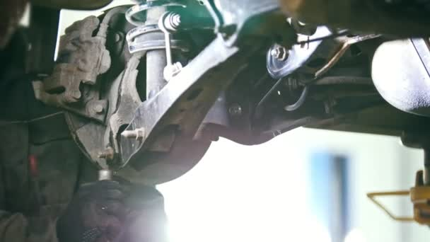 Autoservis auto - mechanik zkontroluje údaje o vozu pod spodní části vozidla
