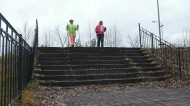 Two elderly women doing Nordic walking in autumn Park outdoor