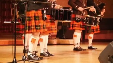 Traditional scottish band musicians singing with bagpipes on the stage