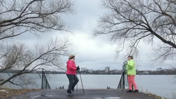 Seniorin im Herbstpark beim Aufwärmen vor Nordic Walking